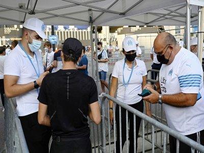 Des employés contrôlent le pass sanitaire de visiteurs au Stade Vélodrome de Marseille le 31 juillet 2021 - Christophe SIMON [AFP]