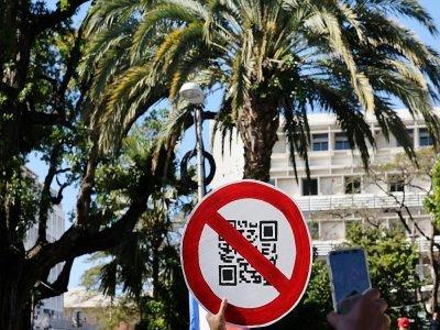 Un manifestant brandit un panneau imitant un QR code lors d'une manifestation contre le pass sanitaire à Saint-Denis de la Réunion le 31 juillet 2021 - Richard BOUHET [AFP]
