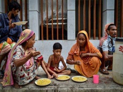 Des personnes apauvries par la crise du coronavirus mangent un repas offert par l'association Mehmankhana, le 26 juillet 2021 à Dacca    Munir Uz zaman [AFP]