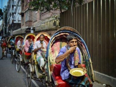 Des personnes affectées par la crise sanitaire mangent un repas offert par l'association Mehmankhana, le 26 juillet 2021 à Dacca    Munir Uz zaman [AFP]