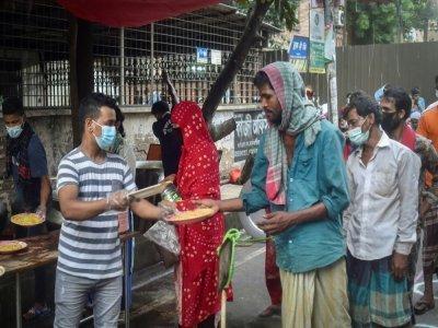 Un bénévole de l'association Mehmankhana distribue des repas à des personnes sans ressources affectées par la crise sanitaire,  le 26 juillet 2021 à Dacca    Munir Uz zaman [AFP]