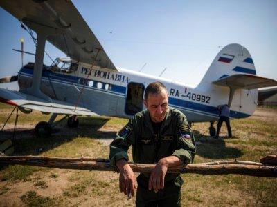 Vladimir Stroyev, pilote du Service aérien de protection des forêts, se repose après un vol d'observation au-dessus des feux de forêt à l'extérieur du village de Berdigestyakh en Sibérie - Dimitar DILKOFF [AFP]