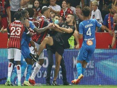 Des joueurs de Nice et de Marseille bloquent un supporter qui tente de donner un coup de pied au joueur marseillais Dimitri Payet (2e g) lors du match de L1 Nice-Marseille interrompu, le 22 août 2021 à Nice    Valery HACHE [AFP]