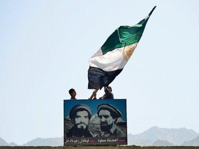Des Afghans agitent un drapeau afghan au-dessus du portrait du commandant Massoud, dans la vallée du Panchir, le 23 août 2021    Ahmad SAHEL ARMAN [AFP]
