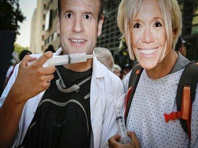 Des manifestants portant des masques d'Emmanuel Macron et de sa femme Brigitte lors d'une manifestation contre le pass sanitaire à Lyon le 14 août 2021    JEAN-PHILIPPE KSIAZEK [AFP]