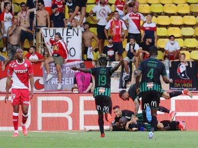 La joie des Lensois après un but marqué contre Monaco, et la déception du défenseur Djibril Sidibé, lors de leur match de Ligue 1, le 21 août 2021 au Stade Louis II - Valery HACHE [AFP/Archives]