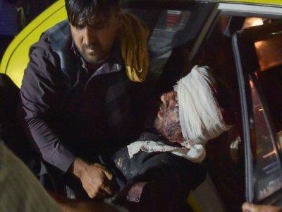 Un membre du personnel de l'hôpital de Kaboul sort d'une voiture un homme blessé dans les deux explosions qui ont frappé l'aéroport de la capitale, le 26 août 2021    Wakil KOHSAR [AFP]