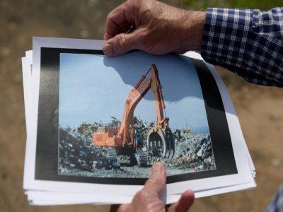 Dennis Diggins montre la photo d'une pelleteuse  en 2001 au milieu des débris du World Trade Center à Fresh Kills, le 28 mai 2021 à Staten Island    Angela Weiss [AFP]