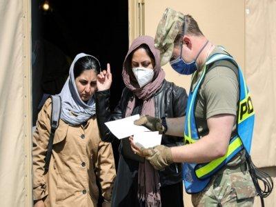 Un soldat américain parle avec des réfugiées afghanes arrivant sur la base aérienne américaine de Ramstein, en Allemagne, le 26 août 2021    Armando BABANI [AFP]
