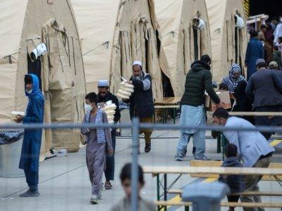 Des réfugiés afghans devant les tentes destinées à les accueillir quelques jours avant leur transfert vers les Etats-Unis, sur la base aérienne américaine de Ramstein, en Allemagne, le 26 août 2021    Armando BABANI [AFP]