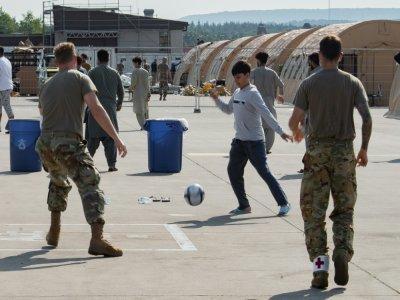 Des enfants afghans jouent au foot avec des soldats américains, sur la base aérienne américaine de Ramstein, en Allemagne, le 26 août 2021. Photo distribué par le service de relations publique de l'armée américaine    Edgar Grimaldo [US Central Command Public Affairs/AFP]