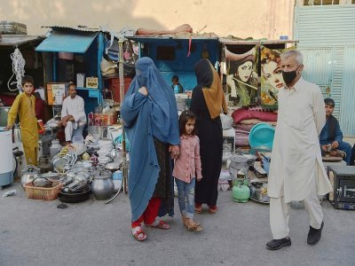 Une femme portant une burqa (c) devant un étal d'un marché de Kaboul, le 25 août 2021    WAKIL KOHSAR [AFP/Archives]