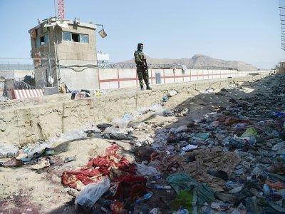 Un combattant taliban se tient face au site d'un attentat à la bombe à l'aéroport de Kaboul le 27 août 2021 - WAKIL KOHSAR [AFP]