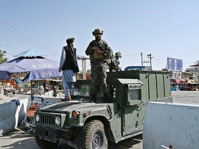 """Des membres de l'unité """"Badri 313"""", une composante des forces spéciales talibanes, dans des véhicules blindés Humvee devant l'entrée principale de l'aéroport de Kaboul, le 28 août 2021 - WAKIL KOHSAR [AFP]"""