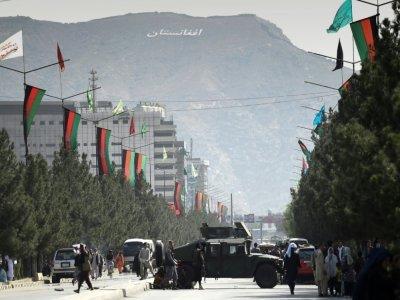 Des talibans bloquent une rue menant à l'aéroport de Kaboul avec un blindé Humvee, le 28 août 2021 - WAKIL KOHSAR [AFP]