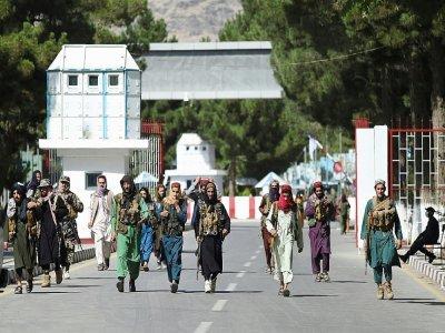 Des combattants talibans marchent devant la principale entrée de l'aéroport de Kaboul, le 28 août 2021 - WAKIL KOHSAR [AFP]