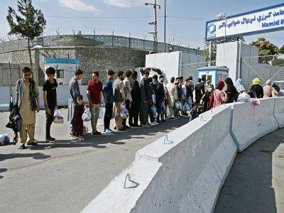 Des Afghans, espérant quitter le pays, font la queue devant l'entrée de l'aéroport de Kaboul, le 29 août 2021    WAKIL KOHSAR [AFP]
