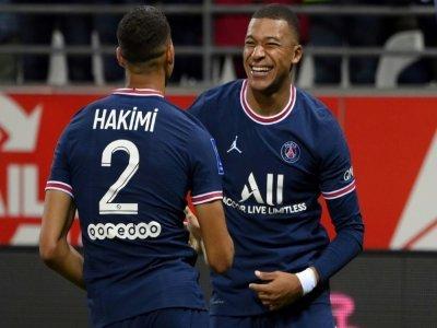 L'attaquant du PSG Kylian Mbappé (d) vient de marquer son second but sur un centre d'Achraf Hakimi (g) à Reims, le 29 août 2021    FRANCK FIFE [AFP]