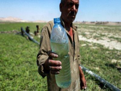 Un homme tient une bouteille d'eau près d'une pompe acheminant de l'eau du lac Assad, le 25 juillet 2021 à Roumeilia, dans le nord de la Syrie    Delil SOULEIMAN [AFP]