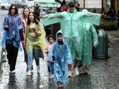 Des touristes des Pays du Golfe sous la pluie dans une rue de Lviv, le 17 août 2021 en Ukraine    Sergei GAPON [AFP]