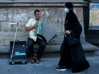 Une touriste des Pays du Golfe passe devant un musicien de rue, le 14 août 2021 à Lviv, en Ukraine    Sergei GAPON [AFP]
