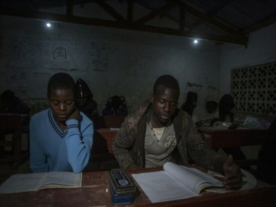 Des écoliers étudient à la lumière des ampoules dans le village de Yobe Nkosi  dans le Nord du Malawi, éclairés grâce à une petite centrale hydro-électrique artisanale    AMOS GUMULIRA [AFP]