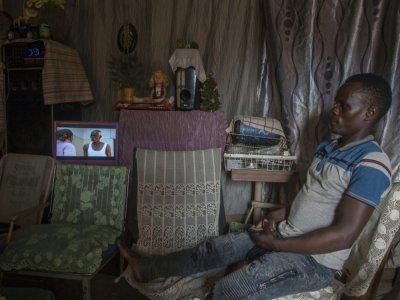 Un homme regarde le 23 août 2021 une télévision alimentée par une petite centrale hydro-électrique artisanale dans le village de Yobe Nkosi, dans le Nord du Malawi    AMOS GUMULIRA [AFP]