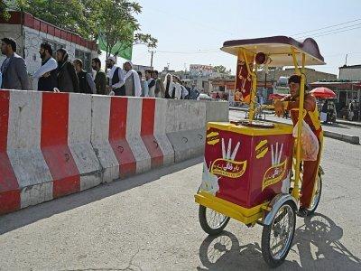 Un vendeur de glaces attend des clients pendant que des employés de l'aéroport de Kaboul font la queue à un point de contrôle pour aller à leur travail, le 4 septembre 2021    Aamir QURESHI [AFP]