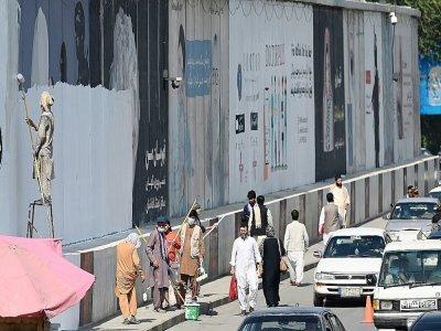 Des peintres recouvrent des inscriptions murales de peinture dans une rue de Kaboul, le 4 septembre 2021    Aamir QURESHI [AFP]