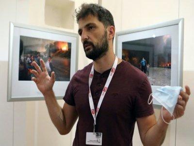 Le photographe grec de l'AFP Angelos Tzortzinis explique les histoires derrière ses photos exposées au festival international du photojournalisme à Perpignan, le 2 septembre 2021    RAYMOND ROIG [AFP]