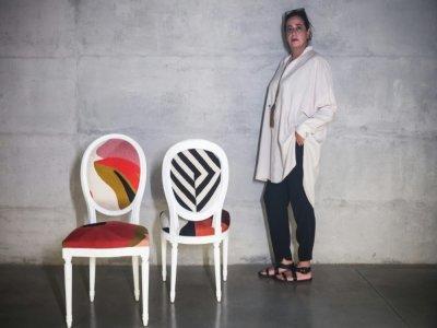 India Mahdavi pose à côté de ses chaises à l'occasion du Fuorisalone 2021 au Palazzo Citterio, le 4 septembre 2021 à Milan    MARCO BERTORELLO [AFP]