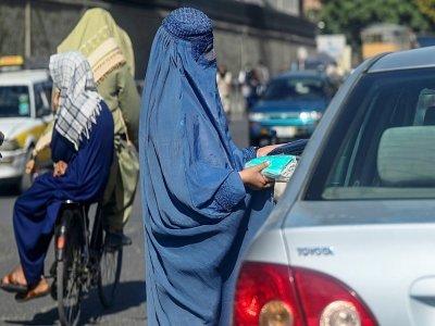 Une Afghane en burqa vend des masques de protection à un automobiliste dans une rue de Kaboul, le 5 septembre 2021    Aamir QURESHI [AFP]