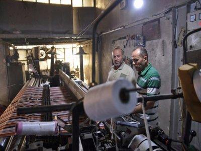 Des ouvriers dans un atelier de confection textile, le 30 août 2021 à Alep, en Syrie    - [AFP]