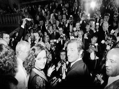 """L'acteur français Jean-Paul Belmondo et l'actrice italienne Laura Antonelli arrivent pour la projection du film """"Stavinsky"""" réalisé par Alain Resnais lors du 27e Festival de Cannes à Cannes, le 13 mai 1974    Ralph Gatti [AFP]"""