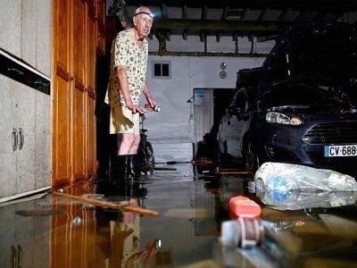 Un homme devant son garage inondé à Agen le 9 septembre 2021    Philippe LOPEZ [AFP]