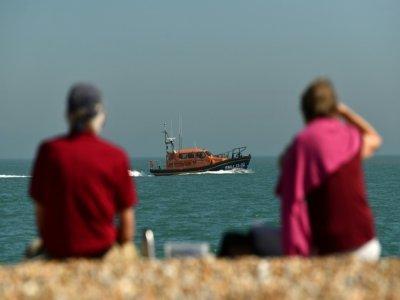 Un couple observe un bateau du secours en mer britannique sur la plage de Dungeness, le 7 septembre 2021, dans le sud-est de l'Angleterre - Ben STANSALL [AFP]