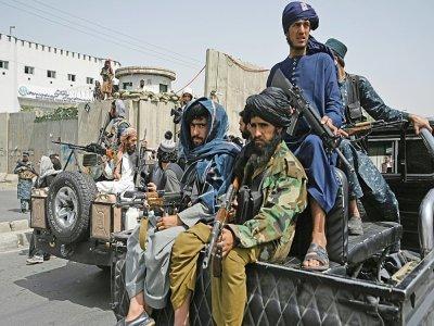 Des combattants talibans armés escortent des Afghanes en niqabs noirs lors d'un rassemblement pro-talibans devant l'Université Shaheed Rabbani, le 11 septembre 2021 à Kaboul    Aamir QURESHI [AFP]