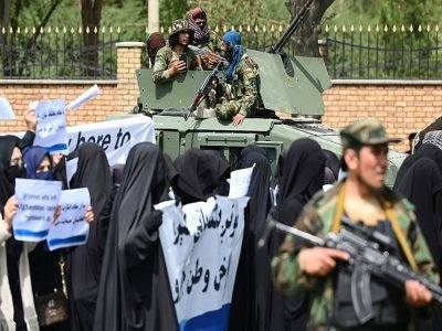 Des combattants talibans encadrent une marche d'Afghanes en niqabs noirs lors d'un rassemblement devant l'Université Shaheed Rabbani, le 11 septembre 2021 à Kaboul    Aamir QURESHI [AFP]