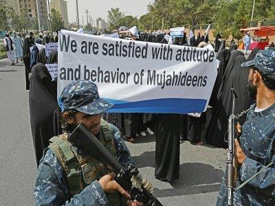 """Des Afghanes en niqabs noirs défilent avec une pancarte """"Nous sommes satisfaites de l'attitude et du comportement des moudjahidines (talibans)"""", devant l'Université Shaheed Rabbani, le 11 septembre 2021 à Kaboul    Aamir QURESHI [AFP]"""
