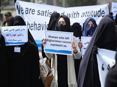 """Une pancarte """"Les femmes qui ont quitté l'Afghanistan ne peuvent pas nous représenter"""" brandie par une Afghane en niqab noir lors d'un rassemblement pro-talibans devant l'université Shaheed Rabbani, le 11 septembre 2021 à Kaboul    Aamir QURESHI [AFP]"""