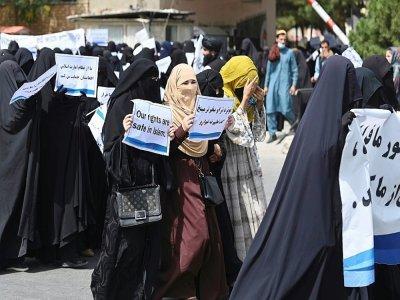 Des Afghanes en niqabs noirs défilent avec des pancartes pro-talibans devant l'université Shaheed Rabbani, le 11 septembre 2021 à Kaboul    Aamir QURESHI [AFP]