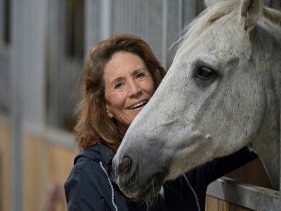 Reha Hutin, présidente de la Fondation 30 Millions d'amis, caresse un cheval au refuge de la Fondation, le 9 septembre 2021 à Bannegon, dans le Cher    GUILLAUME SOUVANT [AFP]