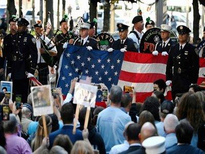 Des policiers et pompiers tiennent le drapeau américain pendant l'hymne national, lors des commémorations pour le 20e anniversaire des attaques du World Trade Center, le 11 septembre 2021 à New York    Jim WATSON [AFP]