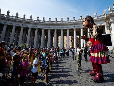 """Des personnes se rassemblent devant """"Little Amal"""" (la petite Amal), une poupée géante représentant une jeune refugiée syrienne sur la place Saint-Pierre au Vatican, le 1O septembre 2021    Tiziana FABI [AFP]"""