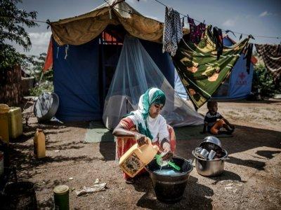Une femme lave des ustensiles de cuisine dans un camp pour réfugiés à Beledweyne, en Somalie, zone en proie à des inondations, le 14 décembre 2019    LUIS TATO [AFP]
