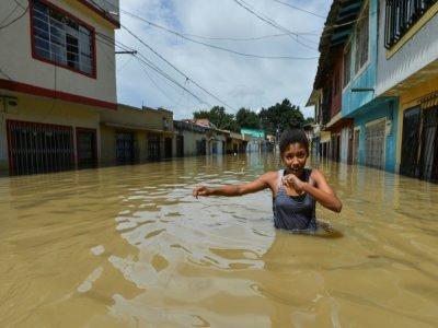 Une fille marche à travers une rue inondée à Cali, en Colombie, le 13 mai 2017    LUIS ROBAYO [AFP/Archives]