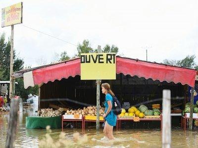 Une femme passe devant un étal de fruits et légumes dans une rue inondée à Codognan, dans le Gard, le 14 septembre 2021, à la suite de fortes pluies    Sylvain THOMAS [AFP]
