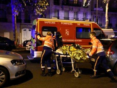 Des pompiers évacuent une personne blessée dans l'attaque du Bataclan, dans le nuit du 13 au 14 novembre 2015 à Paris - MIGUEL MEDINA [AFP/Archives]