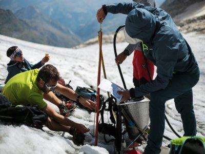 Pierre René (d) effectue des mesures sur le glacier d'Ossoue au pic du Vignemale au sud-ouest de Toulouse dans les Pyrénées le 5 septembre 2021 - Matthieu RONDEL [AFP]