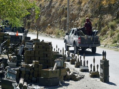 Des combattants talibans passent devant des munitions sur une route du district de Bazark dans le Panchir dont ils ont pris le contrôle, le 15 septembre 2021 - WAKIL KOHSAR [AFP]